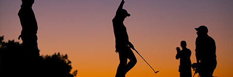 Silhouettes of several golfers in sunset light.