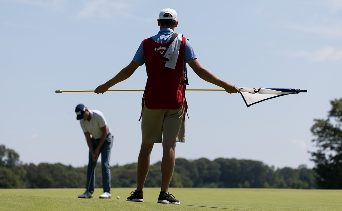 Caddie holding flagstick with player putting in the background
