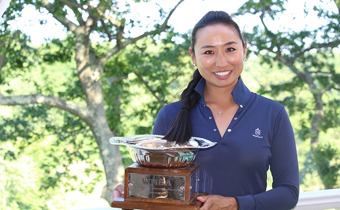 Female golfer holding the 17th WMGA/MGA Women's Met Amateur Championship trophy