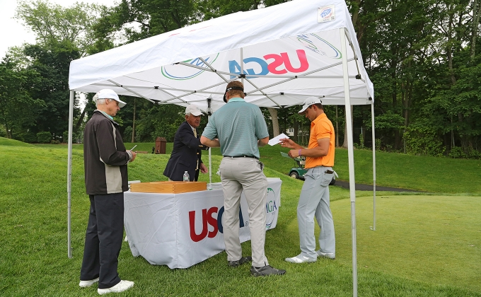 Players and an official at a USGA and MGA tent.