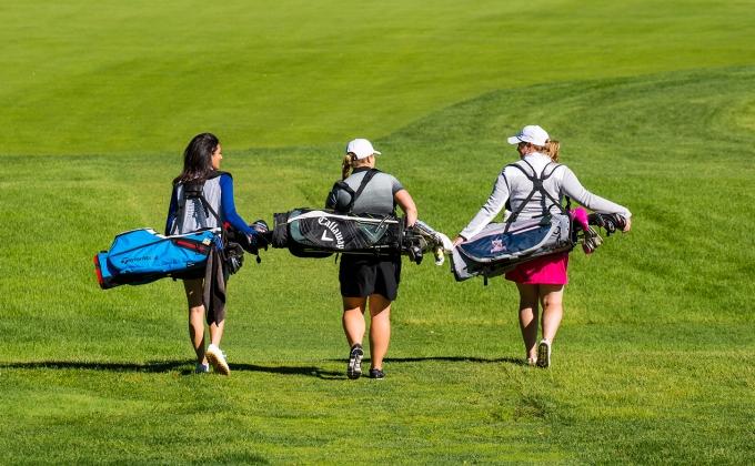 Three women walking down a fairway, carrying their golf bags