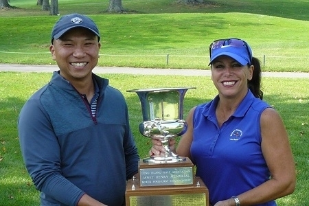 Two golfers holding a trophy