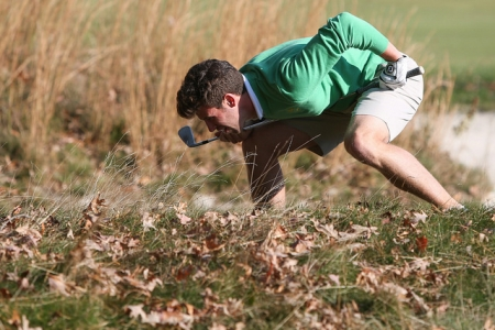 Golfer searching through leaves for golf ball