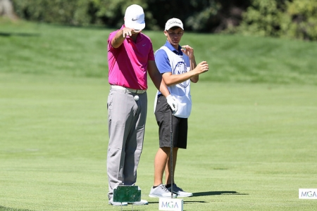 Golfer and caddie standing on fairway