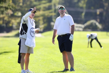 Golfer discussing the game with a caddie