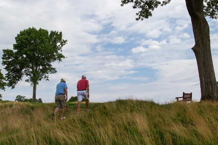 Two men walking through fescue up a hill