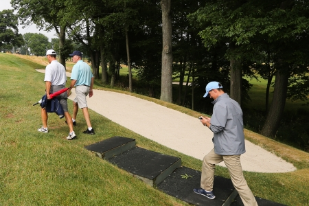 Golfers walking up a green-side staircase