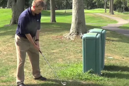 Golfer addressing his ball next to a transformer