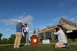 Golfer receiving award with photographer nearby.