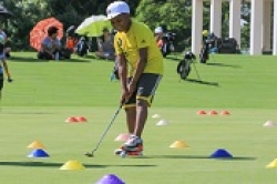 Child golfer practicing putting.