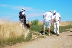 Golfers and caddie near fescue.