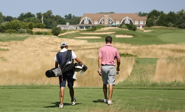 Caddie and golfer walking off the tee