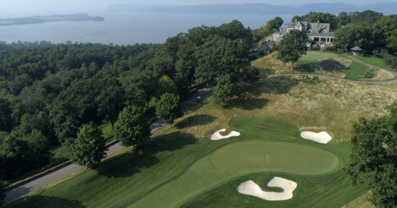 The 18th green and clubhouse at Hudson National Golf Club overlooking the Hudson River