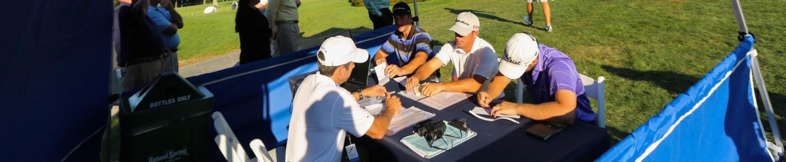 Golfers sitting in a scoring tent
