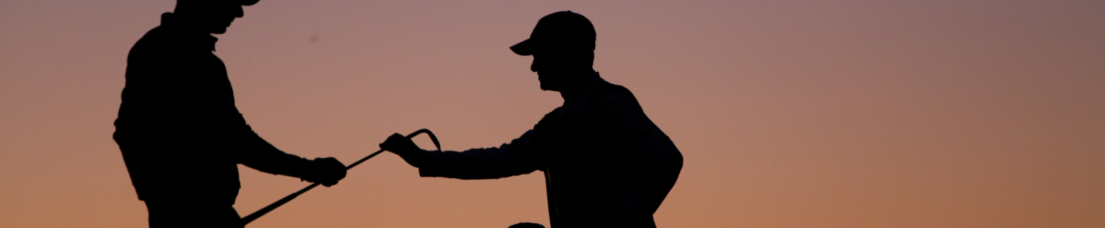 Caddie handing a golfer a club at dusk