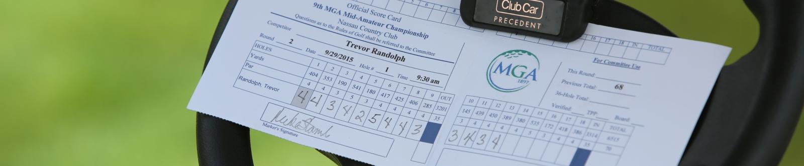 A scorecard on a golf cart steering wheel